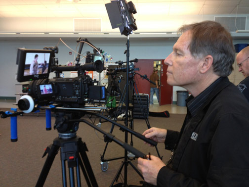 Videographer is operating a large video camera while looking at the actors in his viewfinder.
