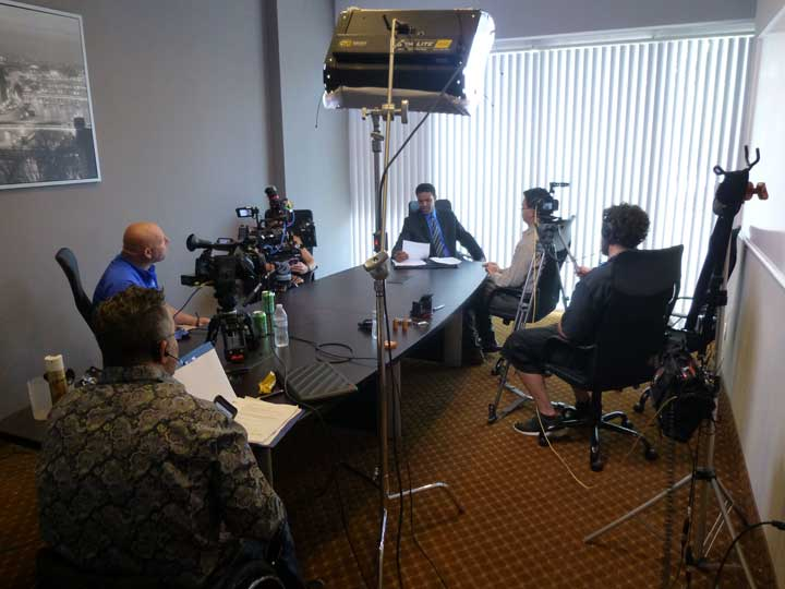 A video production team is sitting around a long conference table. There are cameras and equipment surrounding the actor who is reading his lines on camera.